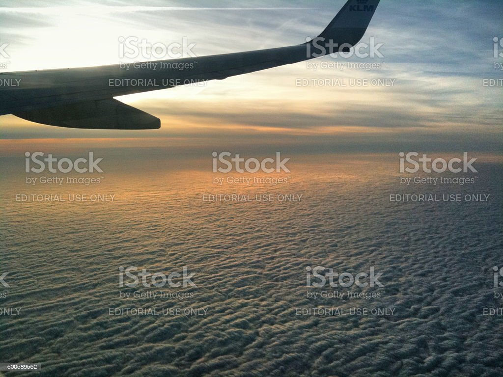 landscape view from airplane porthole KLM airplane over clouds stock photo