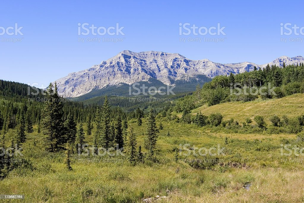 A landscape view of a rocky mountain against a blue sky stock photo