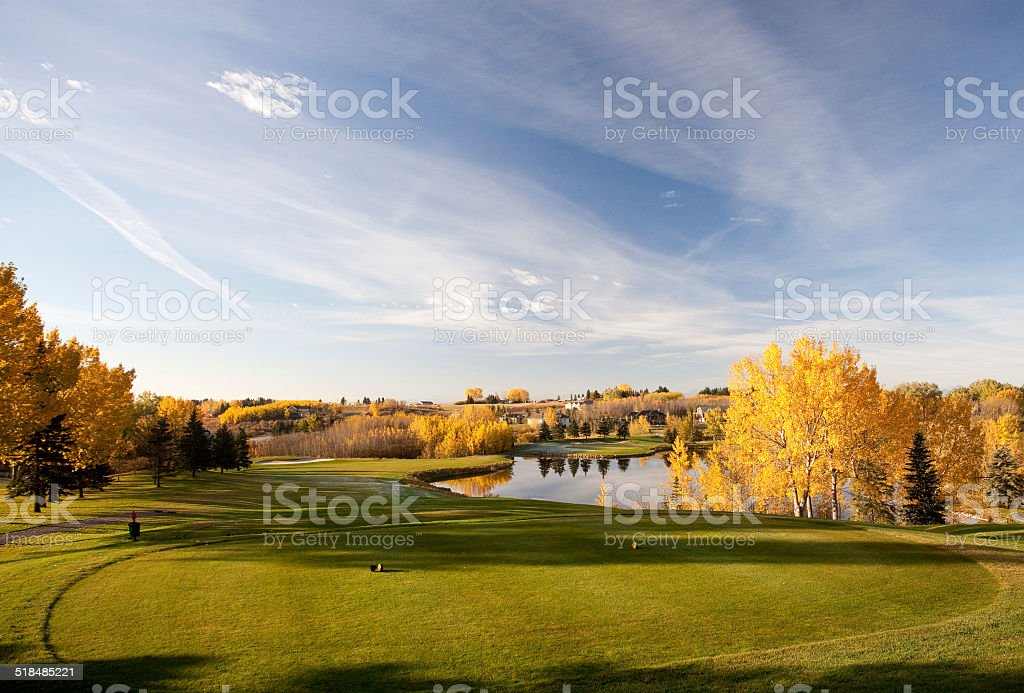 Landscape view of golf course with pond and wooded area. stock photo