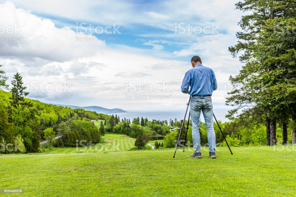 Landscape view of green golf course with hills in summer in La Malbaie, Quebec, Canada in Charlevoix region with photographer and tripod stock photo