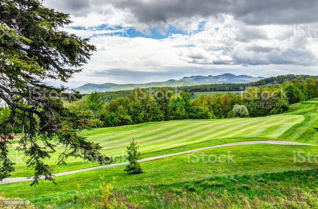 Landscape view of green golf course with hills in summer in La Malbaie, Quebec, Canada in Charlevoix region stock photo