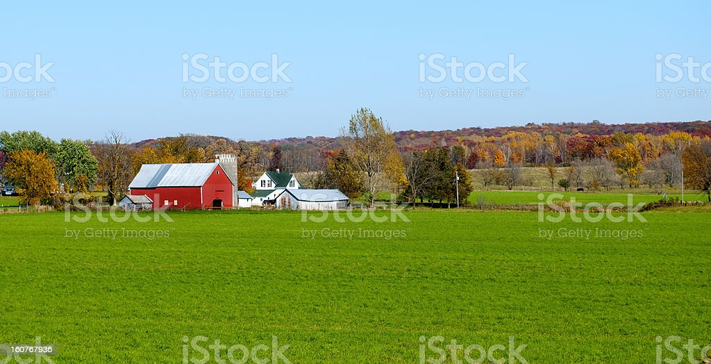 Landscape view of red Midwestern dairy farmhouse and land stock photo