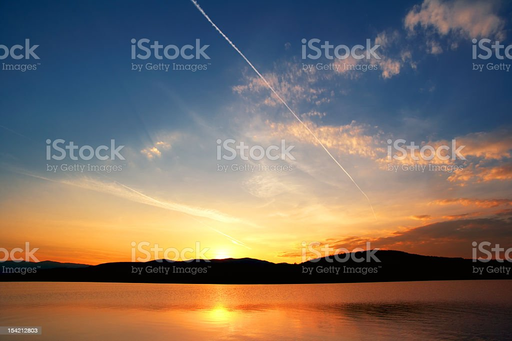 Landscape view of yellow, orange and blue sky at sunset stock photo