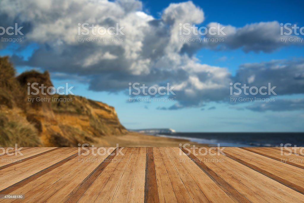 Landscape vivd sunset over beach and cliffs with wooden foreground stock photo