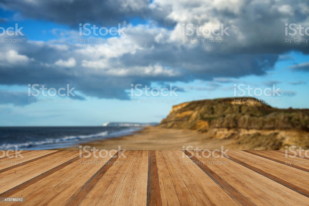 Landscape vivd sunset over beach and cliffs with wooden planks stock photo