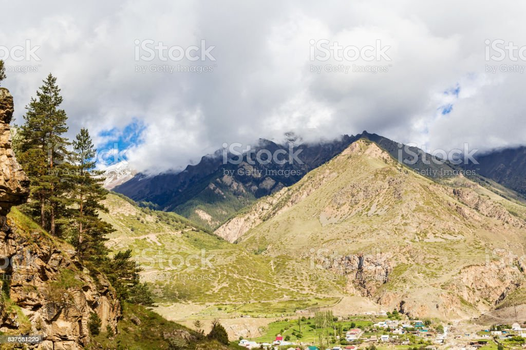 Landscape with a small village at the foot of mountains stock photo