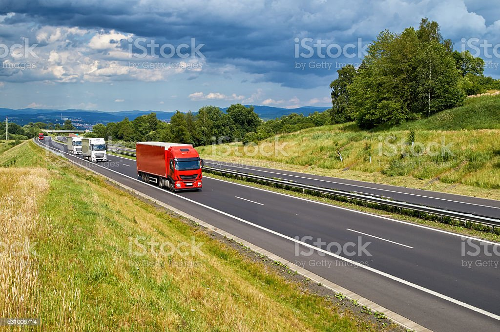 Landscape with an road and a row arriving trucks. stock photo