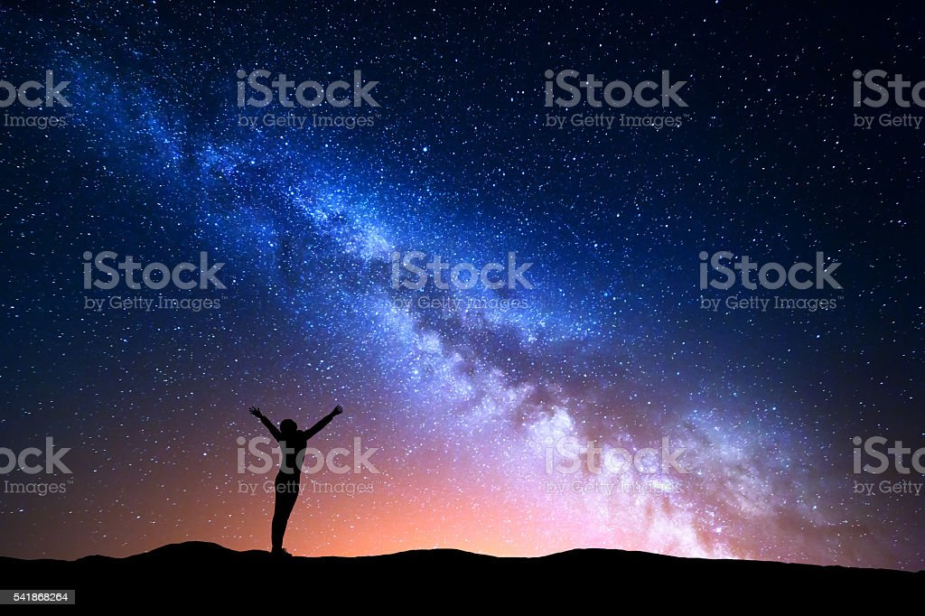 Landscape with blue Milky Way and silhouette of a girl stock photo