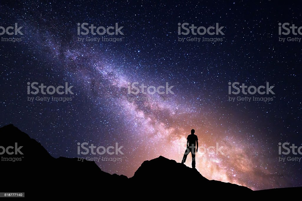 Landscape with Milky Way and silhouette of a happy man stock photo