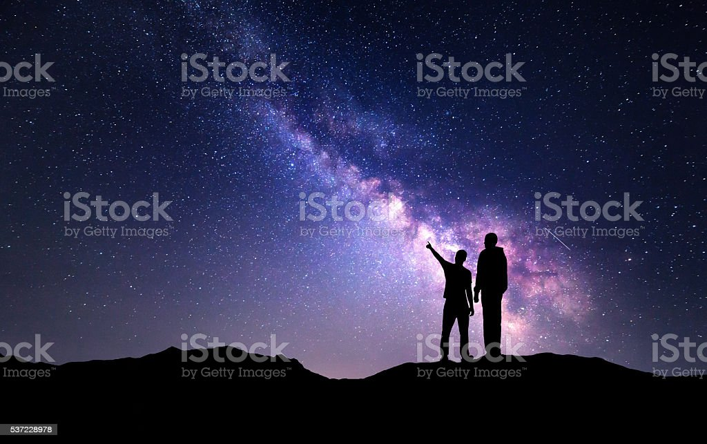 Landscape with Milky Way. Silhouette of a father and son stock photo