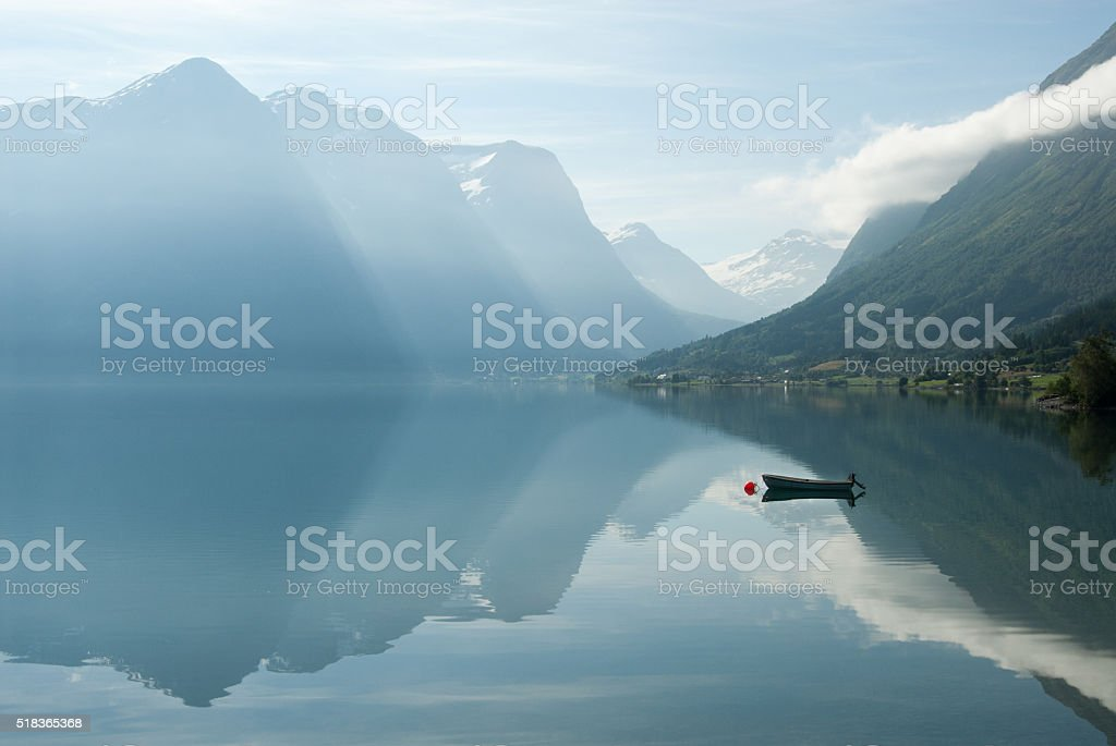 Landscape with mountains reflecting in the water and boat, Norway stock photo