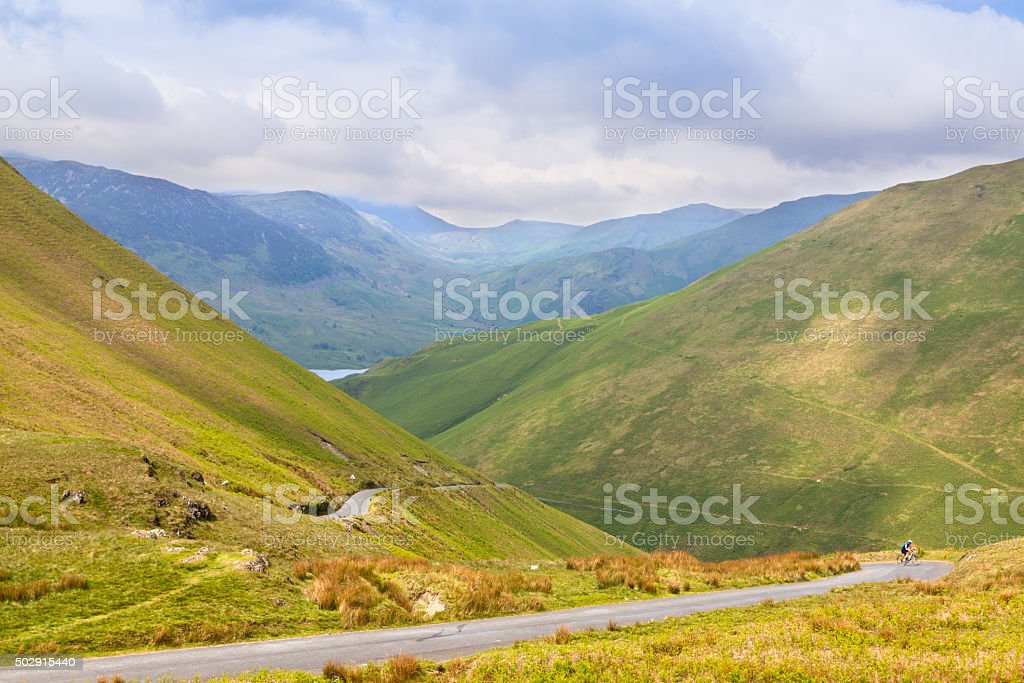Landscape with Mountains, Rural Road and Bicyclist , Lake District, England. stock photo