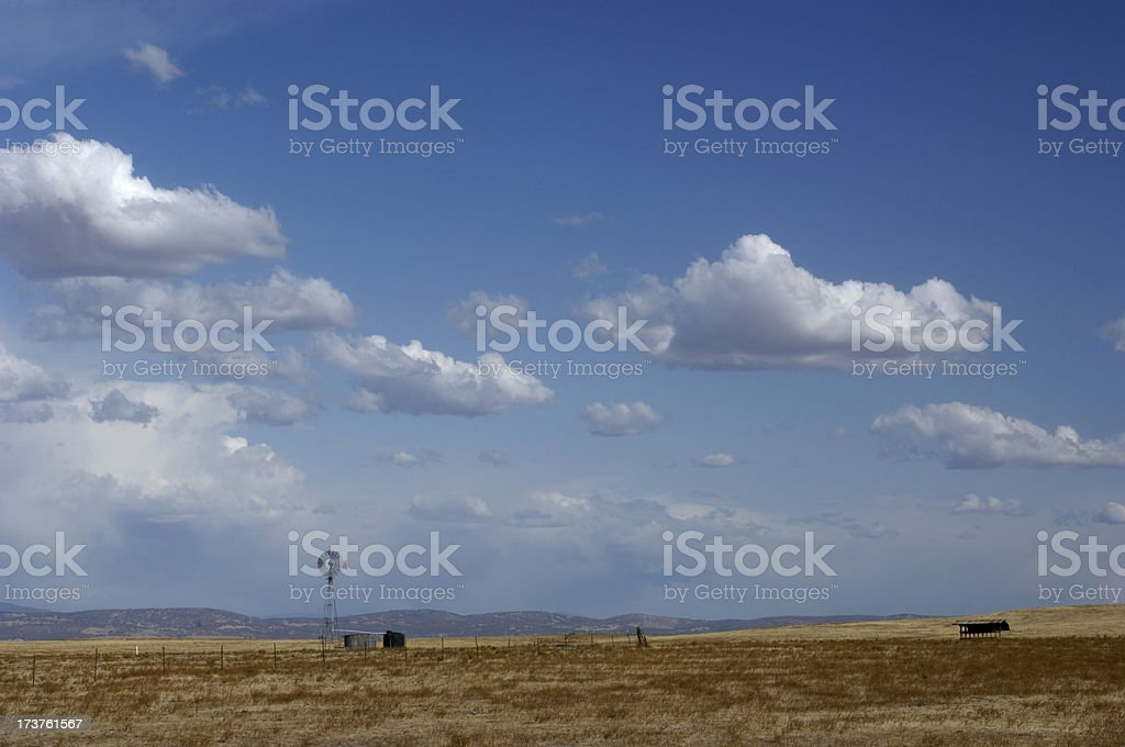 Landscape with Old Windmill and Cloudy Sky in Background royalty-free stock photo