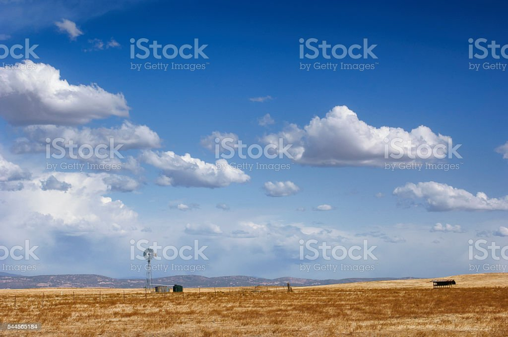 Landscape with Old Windmill and Cloudy Sky in Background stock photo