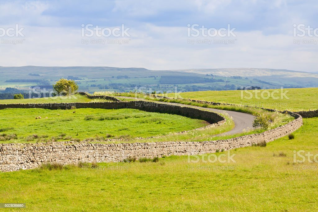 Landscape with Stone Wall and Rural Road, Cumbria, England. stock photo