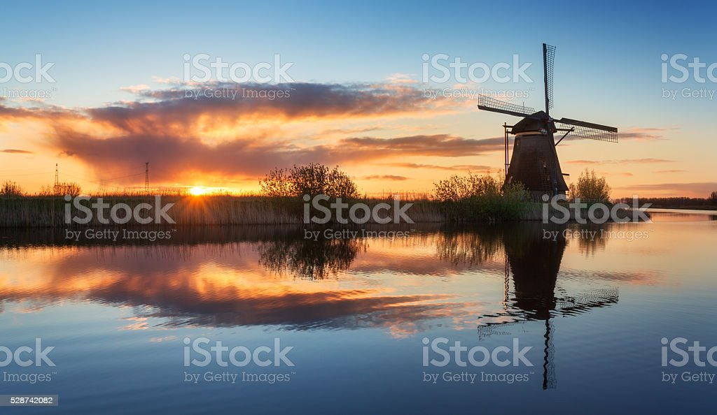 Landscape with traditional dutch windmills at colorful sunrise, beautiful sky stock photo