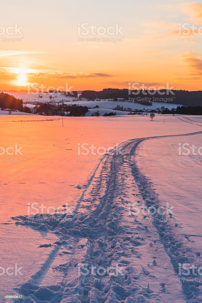 Landscape with trail on snow at sunset stock photo