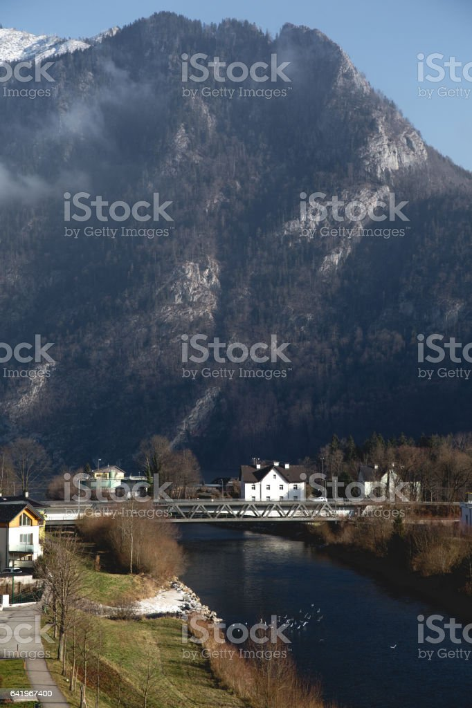 Landscape with white house and metal bridge over river stock photo
