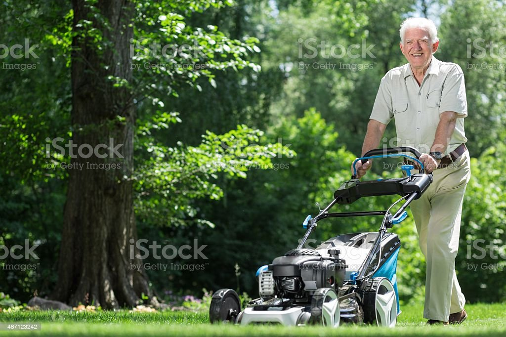 Landscape worker mowing grass stock photo
