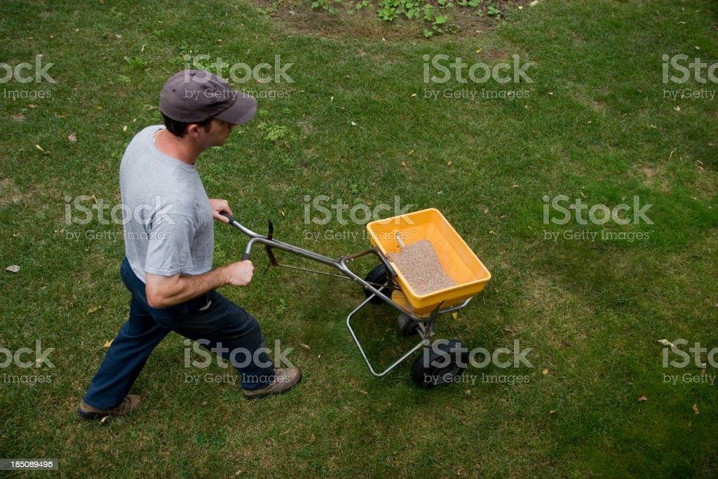 Landscaper Fertilizes a Lawn royalty-free stock photo