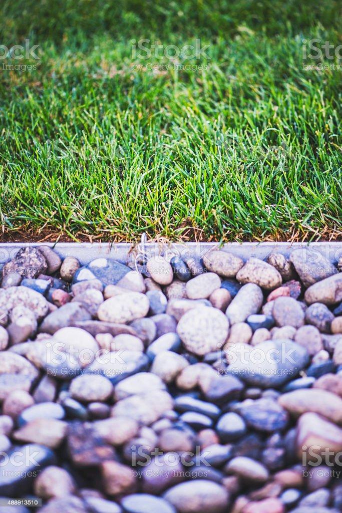 Landscaping: Freshly laid sod next to stone border stock photo