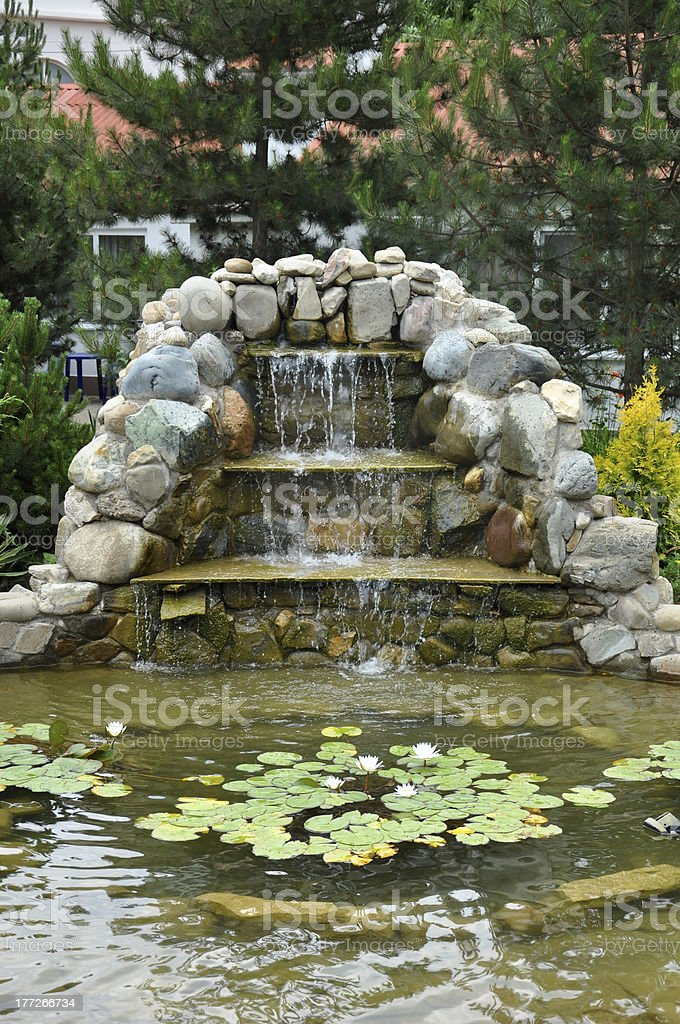 Landscaping - pond with rock slide and waterfall stock photo