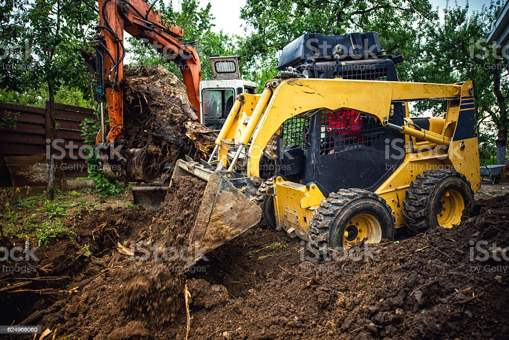 Landscaping works with bulldozer and excavator at home construction site stock photo