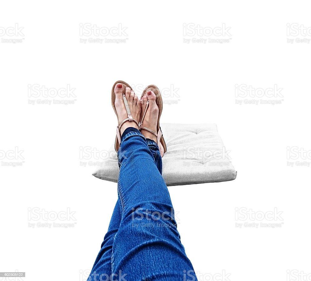 lange Beine mit Sandaletten an den F�ssen auf einem Kissen stock photo