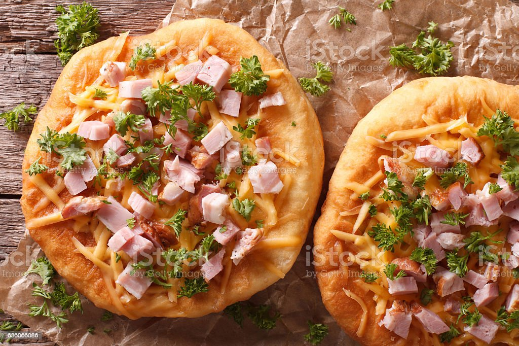 langos deep fried with cheese and ham close-up. Horizontal stock photo