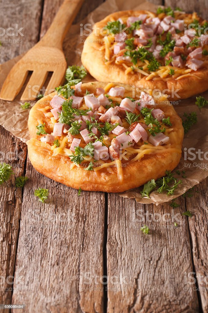 langos deep fried with cheese and ham close-up. vertical stock photo
