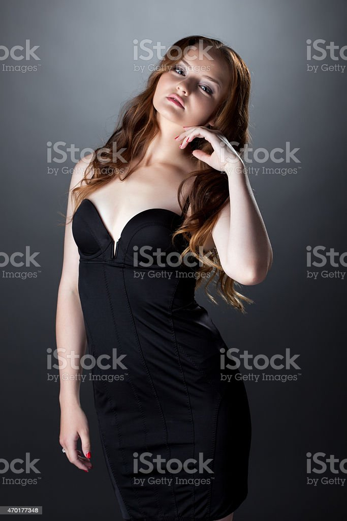 Languid red-haired girl posing in skin-tight dress stock photo