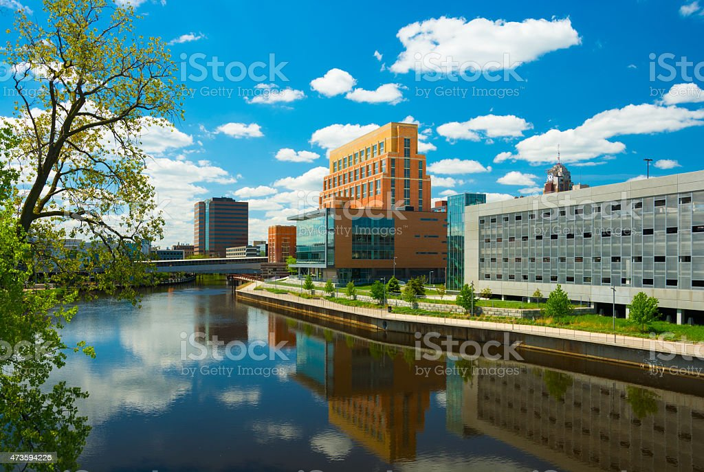 Lansing downtown buildings and Grand River with clouds stock photo