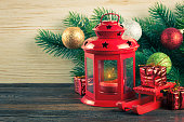 Lantern and Christmas tree over snow on wooden background
