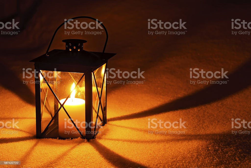 Lantern in snow with warm candlelight royalty-free stock photo
