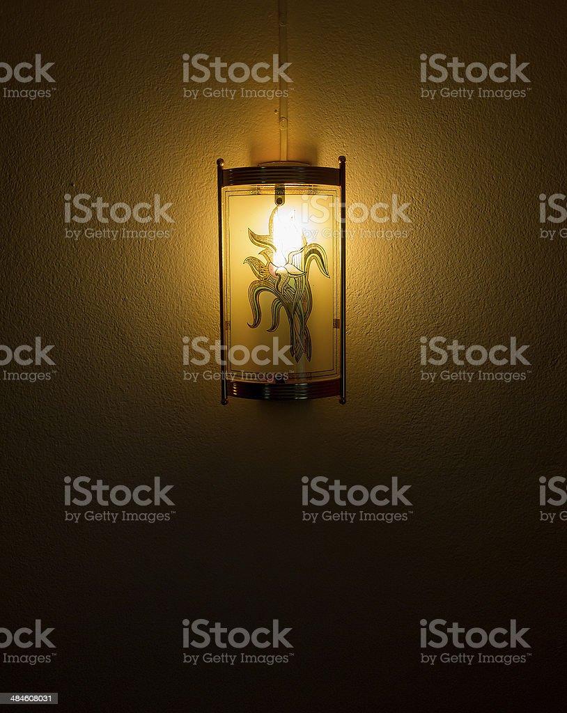 Lantern shining in the dark fixed on the wall stock photo