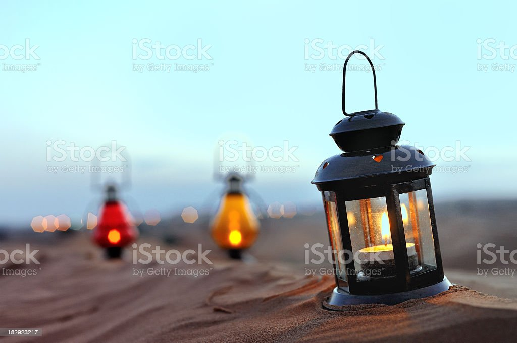 Lanterns with candles in a sandy setting royalty-free stock photo