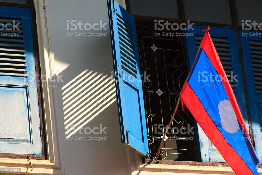 Laos: Lao Flag Hanging from Blue-Shuttered Window, Luang Prabang stock photo
