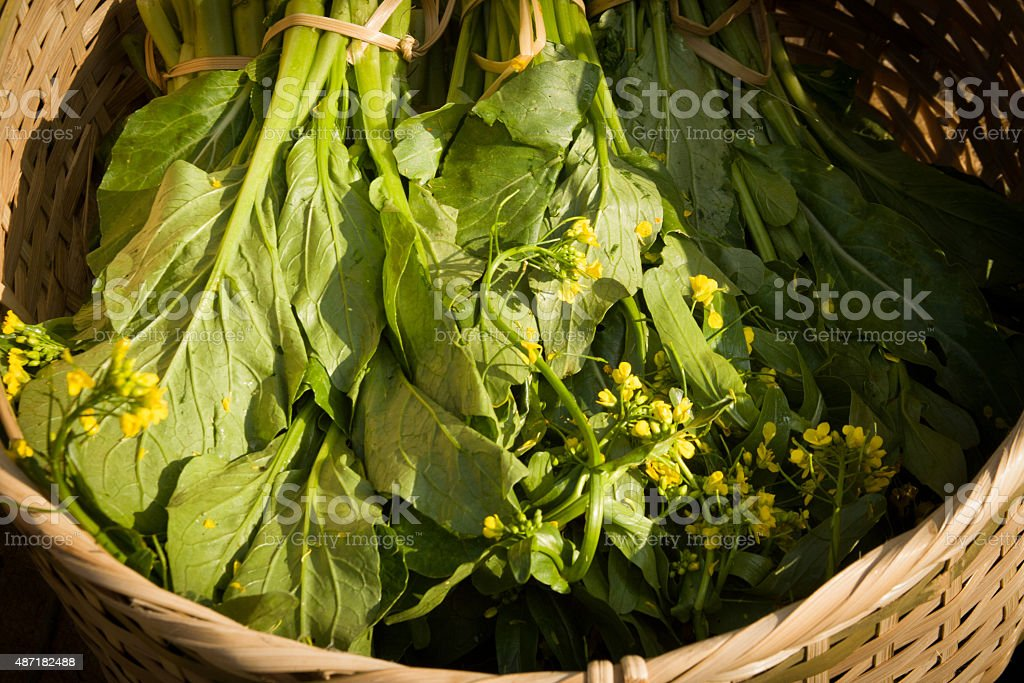 Laos: Mustard Greens with Yellow Flowers Wicker Basket stock photo