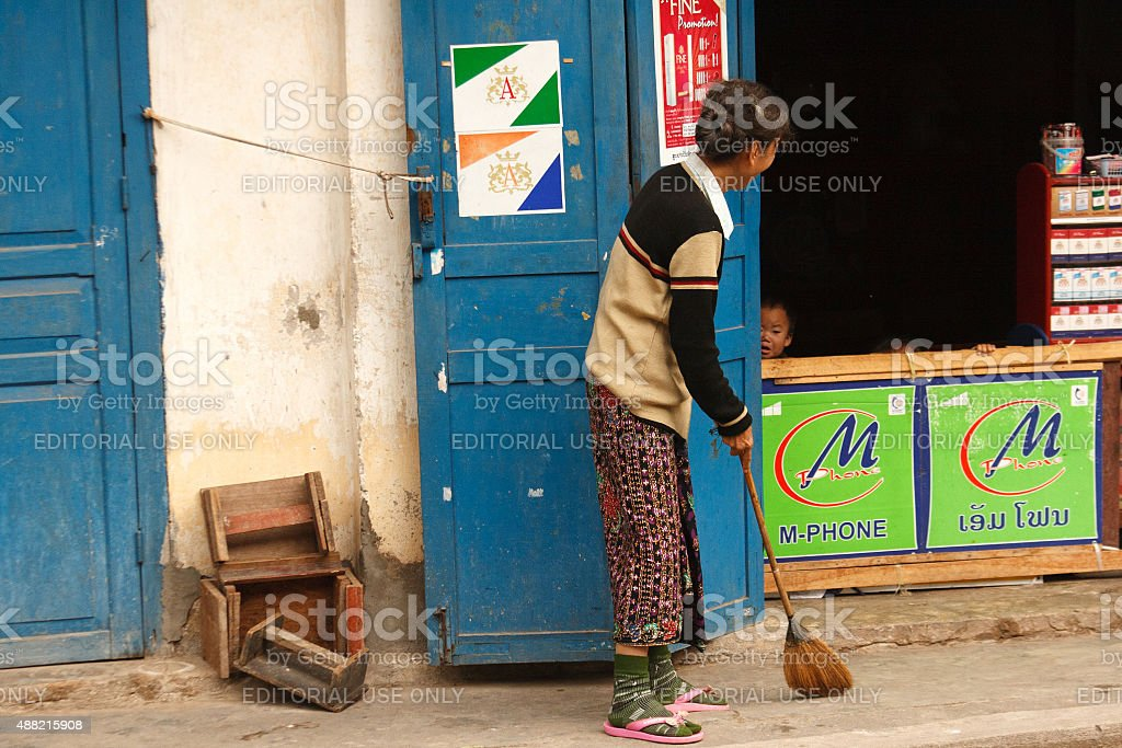 Laos: Senior Woman Sweeping Sidewalk, Child, Blue Doors, Luang Prabang stock photo