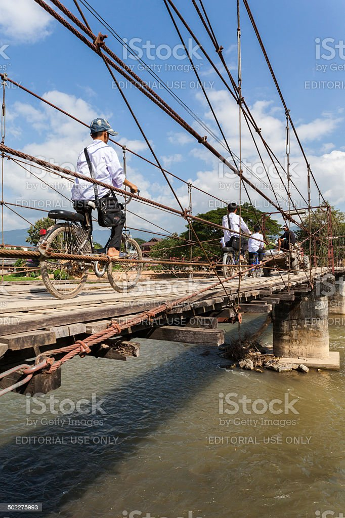 Laotian school children on a wooden bridge in Vang Vieng stock photo