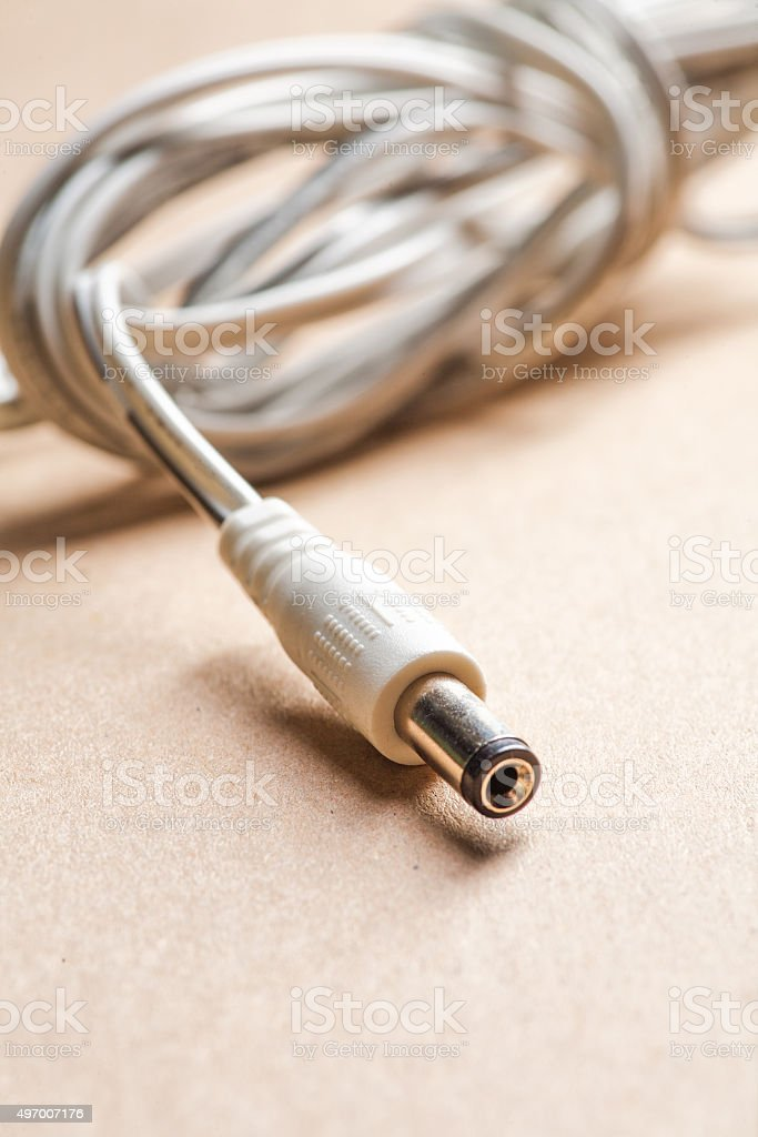 Laptop AC adapter plug on brown craft paper stock photo