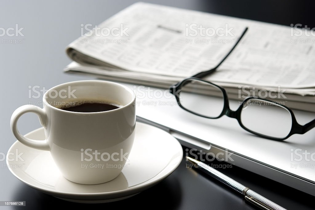 Laptop and a cup of coffee on office desk stock photo