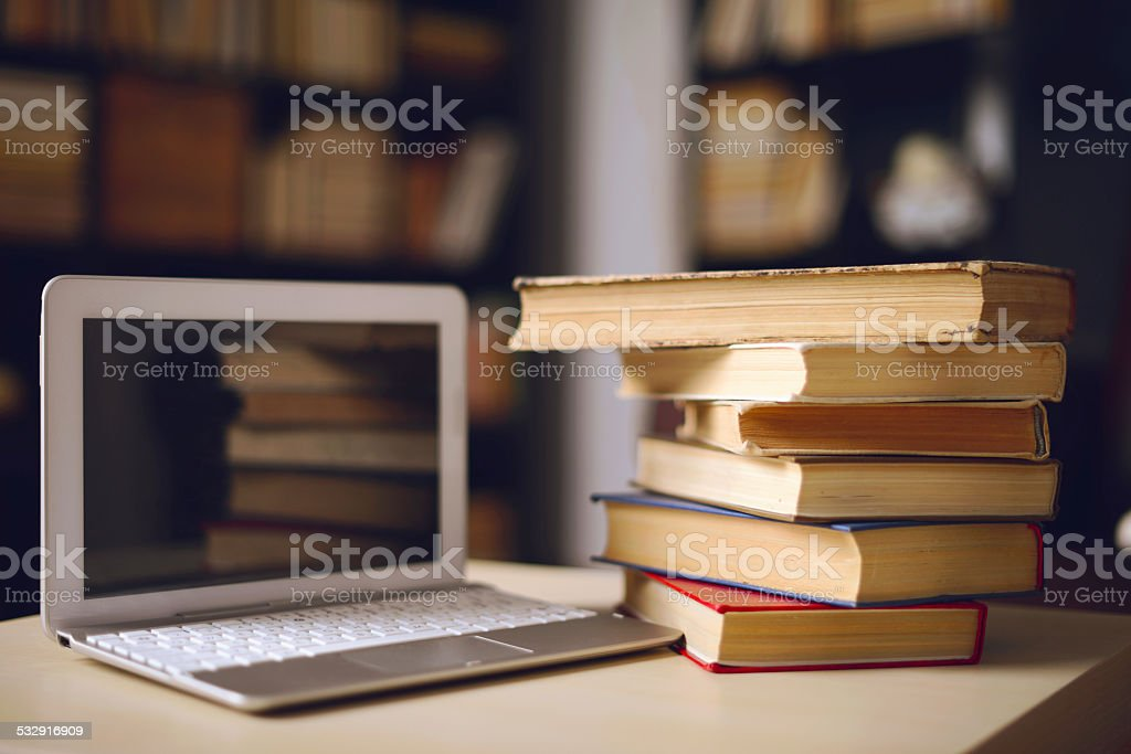laptop and books on the table in the room stock photo