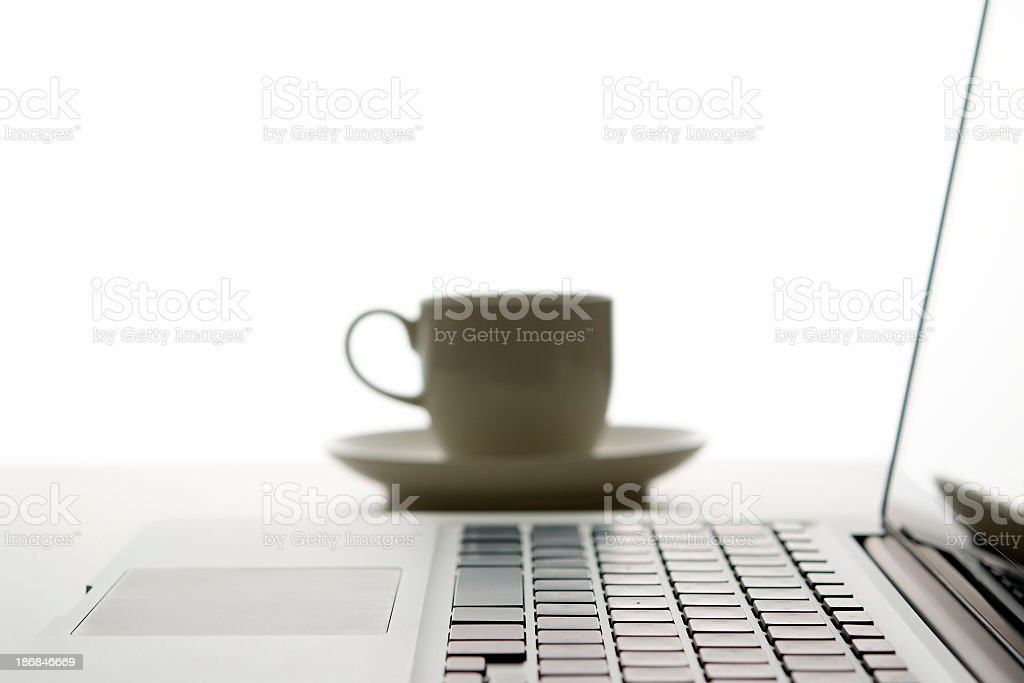 Laptop and coffee cup with shallow depth of field royalty-free stock photo