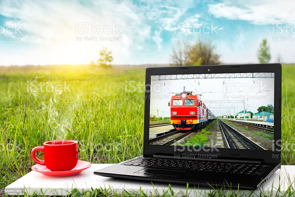 Laptop and cup of hot coffee. Traveling by train. stock photo