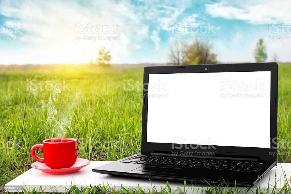 Laptop and cup of hot coffee with blank screen stock photo