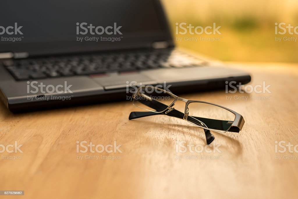 Laptop and glasses on wood table stock photo