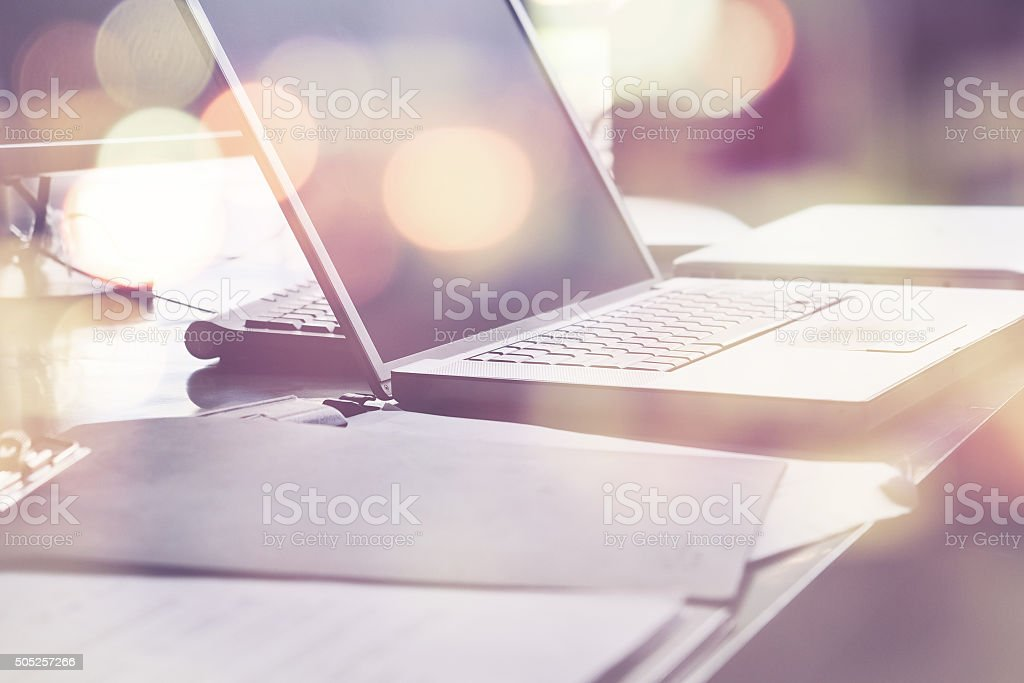 Laptop and papers on desk stock photo