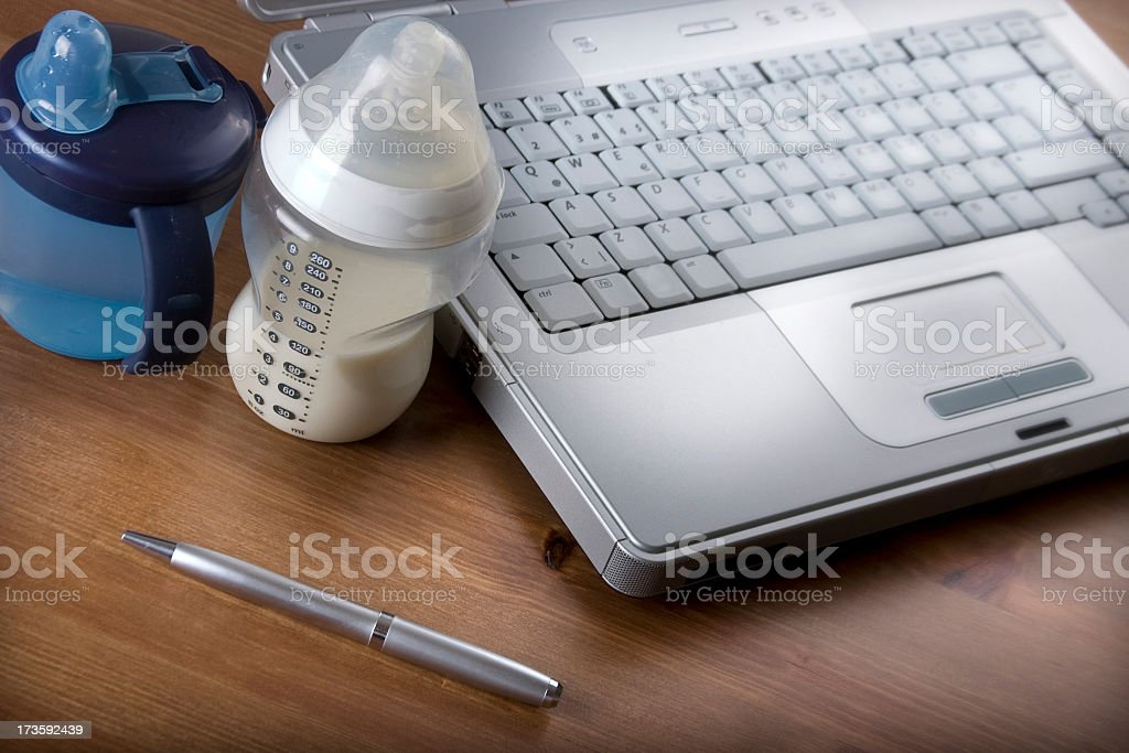 Laptop and pen next to baby bottle and toddler cup stock photo