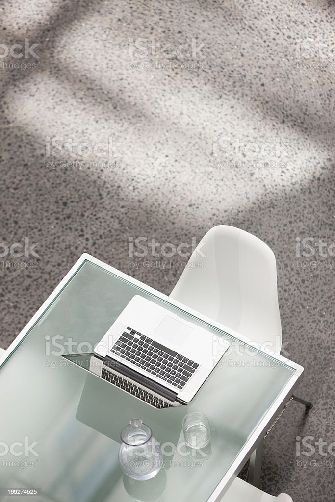 Laptop and water glass on conference table royalty-free stock photo
